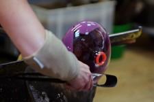 Glaskünstler bei heißer Arbeit: Das Rot an der Öffung ist keine Farbe, es ist noch glühendes Glas.